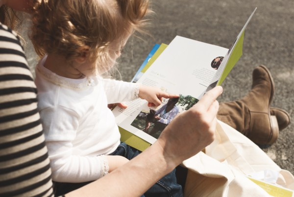Child sitting on her mother's lap reading in a brochure by aspern Seestadt